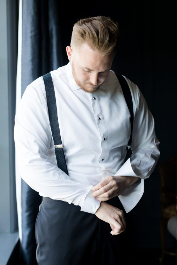 groom prepping on his wedding day in black an white suspender tux