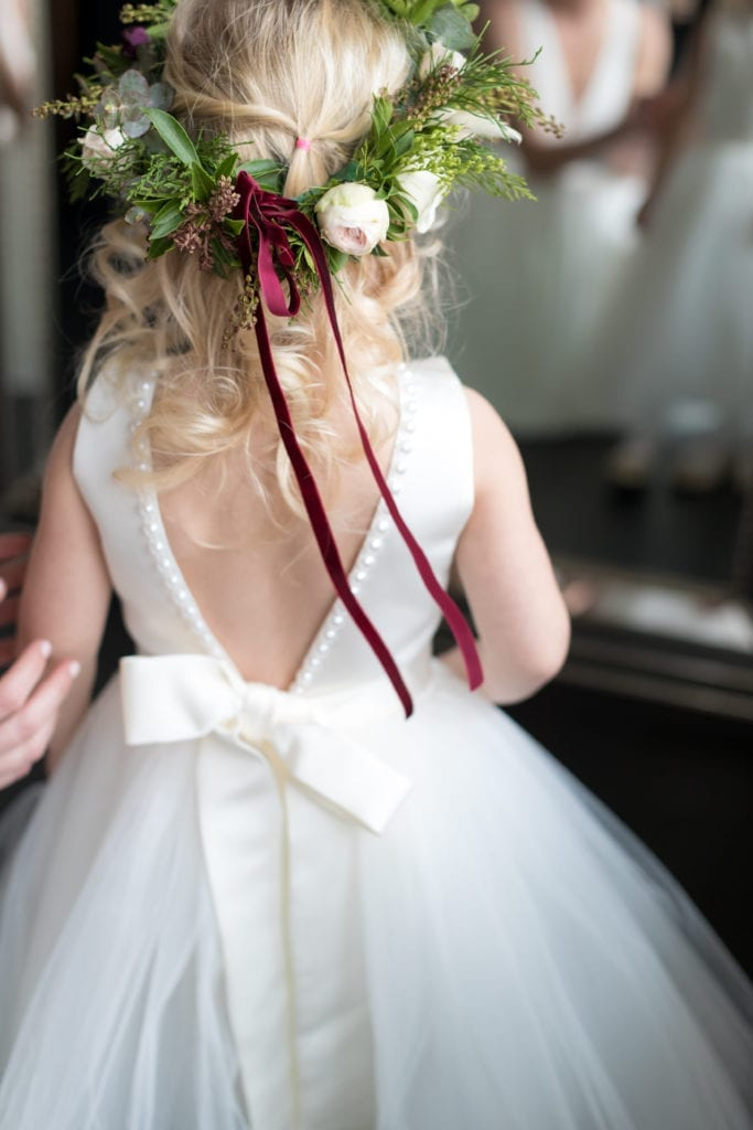 details of flower girls dress and floral headpiece