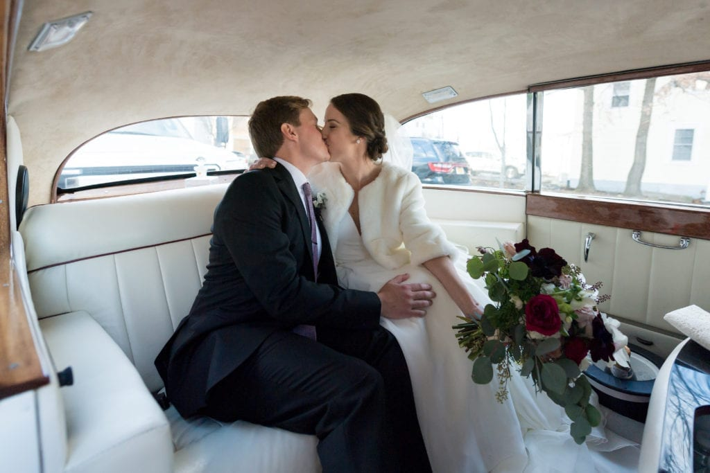 bride and groom in the car after the wedding sharing a kiss