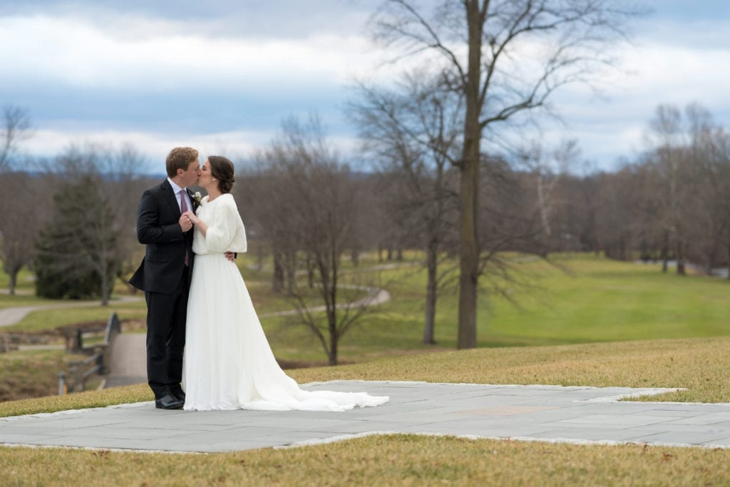 bride and groom kissing on golf course