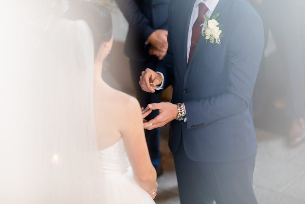 groom putting ring on his bride