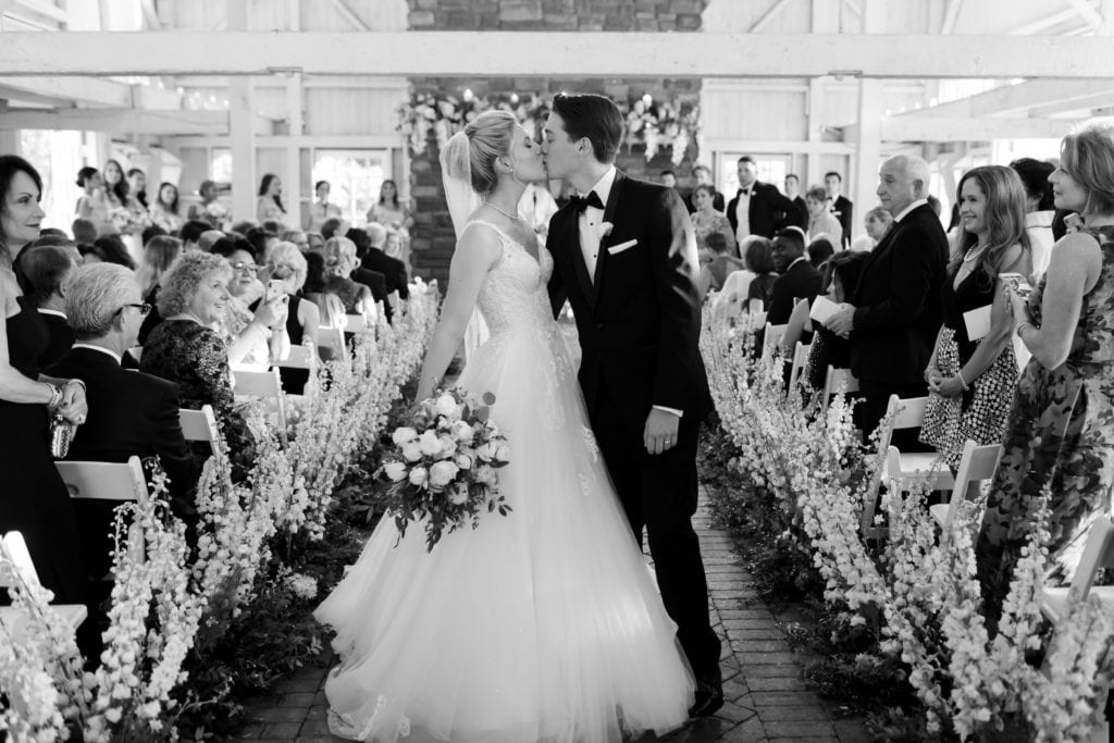 black and white photo of bride kissing at exiting their ceremony